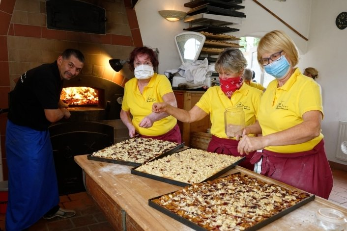 Thomas Götz steht am Ofen, Betty Deml, Christa Klein und Simone Thurn (v.l.) geben dem Blechkuchen den letzten Schliff.
