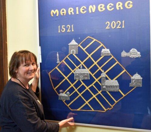 Anett Schlenther vom Team der Baldauf-Villa freut sich über das Geschenk, das im Foyer angebracht wird.