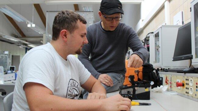 Elektrotechniker-Ausbildung: Ausbilder Hendrik Morgner erklärt Max Vogel die Installation und Wirkungsweise von Glasfasern.