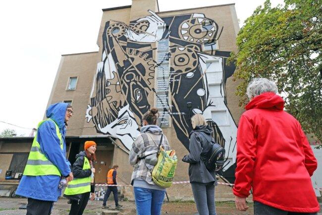 Die ehrenamtlichen Kulturvermittler Cindy Kästner und Oxana Okunew (v.l.) bei einer Führung von Besuchern über das Gelände der IBUG in der Buntpapierfabrik Flöha.