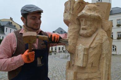 Johannes Düring hat sich am Freitag beim Schnitzen der Bergmannsskulptur, wie sie einst Gotthard Richer schuf, auf dem Schneeberger Markt über die Schulter schauen lassen.