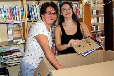 """Ute (l.) und Viktoria Tyrner packen Bücherkisten für den Umzug in die alte Schule. Denn die angestammten Räume der Bibliothek im Gebäude des Museums """"Alte Dorfschule"""" werden saniert."""