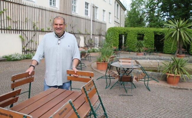 """Maik Hunger rückt im Außenbereich der Gaststätte """"Vitzthum"""" in Lichtenwalde die Stühle zurecht. 100 Plätze stehen zur Verfügung."""
