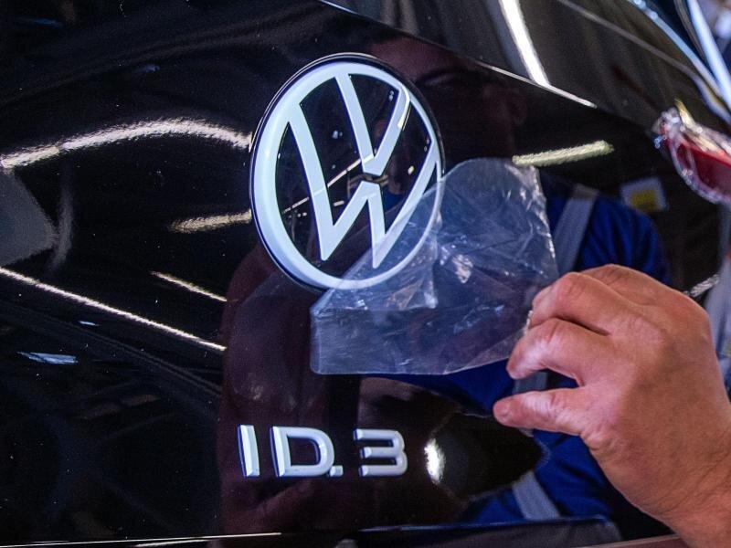 Ein Mitarbeiter entfernt eine Schutzfolie vom VW-Logo am Montageband für das Elektroauto ID.3.