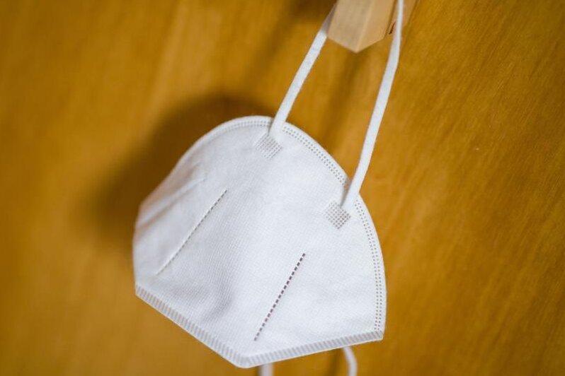 Eine FFP2-Maske hängt an einemHaken. (Archivbild).