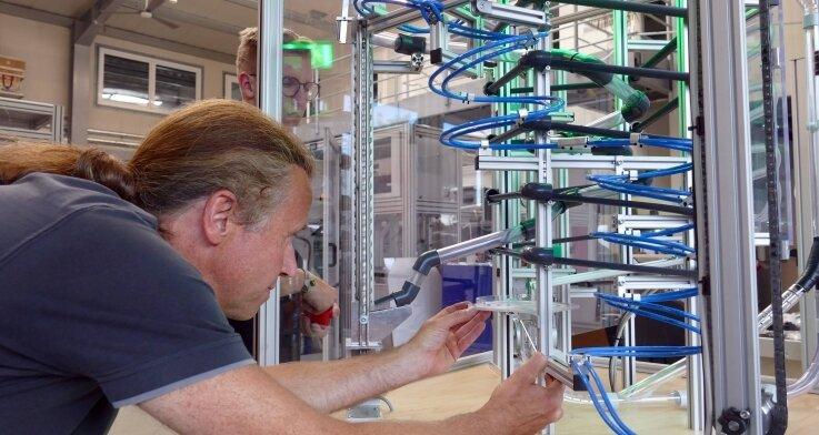Mechaniker Heiko Preißler (vorn) und Azubi Richard Lindner nehmen sich noch einmal die Feinjustierungen an der Murmelbahn vor. Nun ist sie in Seiffen zu sehen.