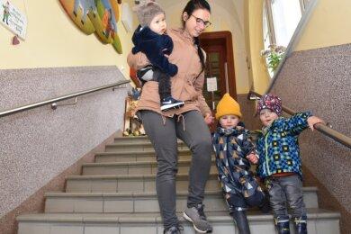 Erzieherin Miriam Kugler mit Krippenkindern auf der Treppe der Adorfer Tagesstätte Zwergenvilla. Sie sind für kleine Füße eine große Hürde. Ein Neubau soll ebenerdig werden, um das Problem zu lösen.