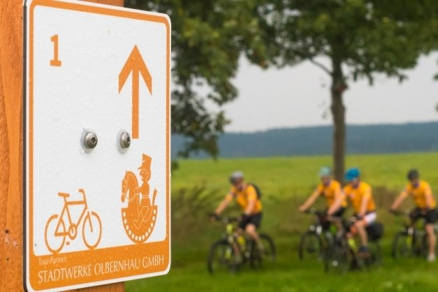 Orangefarbene Tafeln weisen Radsportlern auf der Schwarzwassertal-Tour den richtigen Weg.
