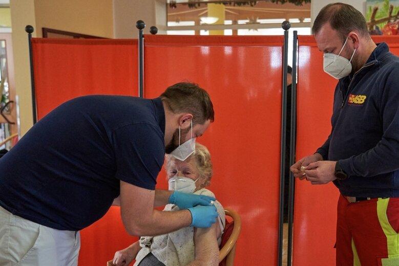 Hilde Kaulfuß, 90-jährige Bewohnerin des Seniorenbetreuungszentrums der gemeinnützigen Heim-Gesellschaft in Glösa, war die erste, die am Silvestertag eine Corona-Schutzimpfung erhielt. Ab dem Morgen waren Christian Homburg und Ben Fischer vom Arbeiter-Samariter-Bund im Impf-Einsatz.