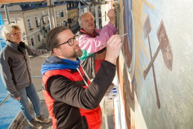 Kati Böckelmann, Daniel Görner (M.) und Adelbert Gründig sanieren gemeinsam die Gemälde an der Marienberger Rathausfassade.
