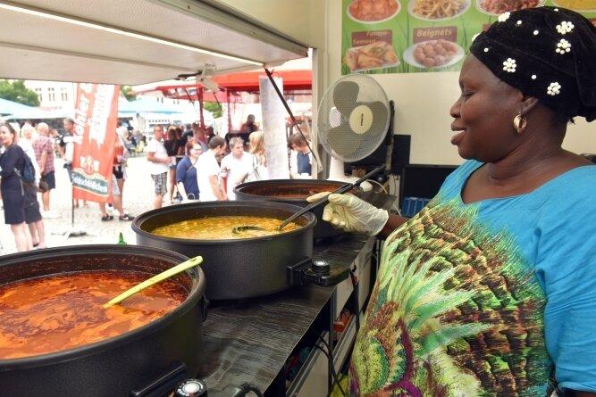 Nationalgerichte aus Gambia servierte Frau Amie am Stand von Gibba Karafa. Yassa und Domoda hießen einige ihrer köchelnden Speisen.