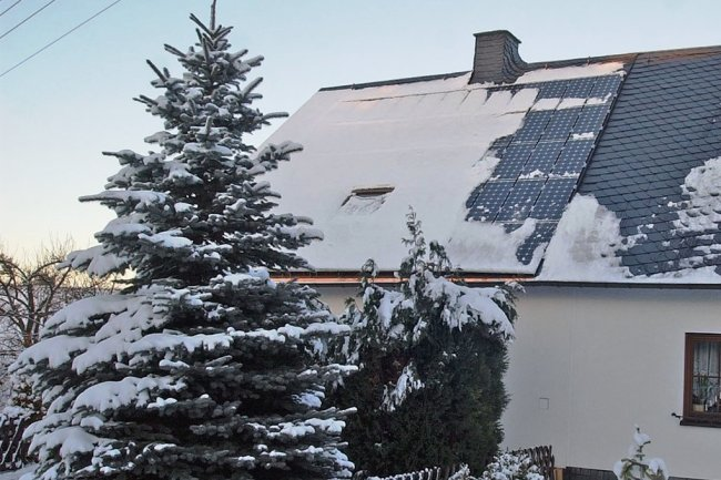 Schnee, wie hier auf einer Photovoltaik-Anlage auf einem Dach, verringert zurzeit die Produktion von Ökostrom in Sachsen.