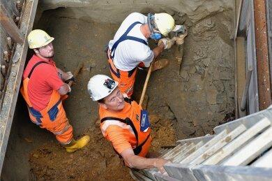 Bauleiter Steffen Rößler (vorn) und seine Kollegen vom Schachtbau Nordhausen in der Baugrube gleich neben der Straße Am alten Bahnhof. Etwa drei Meter unter der Oberfläche stießen sie hier auf einen alten Grubenbau.