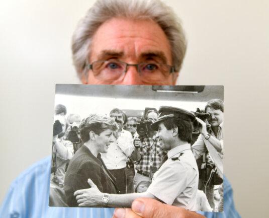 Dieter Kallbach zeigt ein schwarz-weiß Foto vom 23.10.1989, das ihn und die damalige Bürgermeisterin von Stölln, Sybille Heling, zeigt. Das Foto wurde gleich nach der Landung der IL-62 der ehemaligen DDR-Fluggesellschaft Interflug aufgenommen.