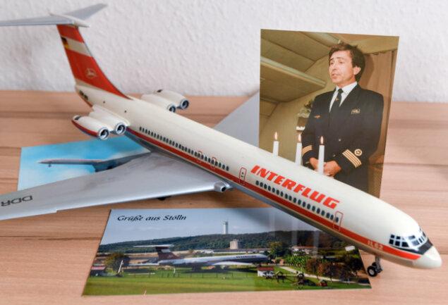 Auf einem Foto ist der Pilot Heinz-Dieter Kallbach neben einem Modell einer IL-62 der ehemaligen DDR-Fluggesellschaft Interflug und einer Postkarte aus Stölln zu sehen.