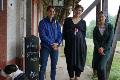 Seit Wochen werkeln Veronika Vaculíková (Mitte) und Alex Mo (rechts) am Bahnhofsgebäude. Unterstützung bekamen sie von vielen Freiwilligen, wie Mara (links), eine Kunststudentin aus dem Libanon.