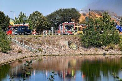 Das Strohballenlager in Berbersdorf hat auch am Freitagvormittag noch gebrannt, 30 Feuerwehrleute waren noch im Einsatz. Ein Regenrückhaltebecken ist gleich auf der anderen Straßenseite.
