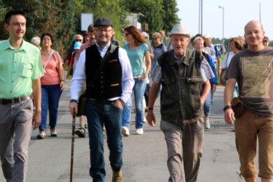 Begleitet von rund 60 Wanderfreunden begeben sich Bürgermeister René Straßberger (v. l.) sowie die Mitglieder der IG Ortsentwicklung, Steffen Schmieder, Horst Hermsdorf und Dirk Schmidt, auf den Rundweg.