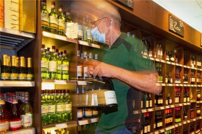 Gestellte Szene vor einem Weinregal: Das Alkoholangebot in deutschen Supermärkten ist riesig und verführerisch.