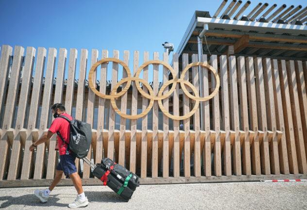 Ein Mann vom Team Mexiko geht an Olympischen Ringen am Eingang vom Olympic Village vorbei. Das olympische Dorf ist eine Wohnsiedlung, in der die Teilnehmer der Olympischen Spiele 2020 untergebracht sind.