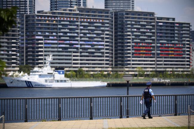 Ein  Polizist patrouilliert vor einem Boot der japanischen Küstenwache vor dem Olympic Village . Das olympische Dorf ist eine Wohnsiedlung, in der die Teilnehmer der Olympischen Spiele 2020 untergebracht sind.