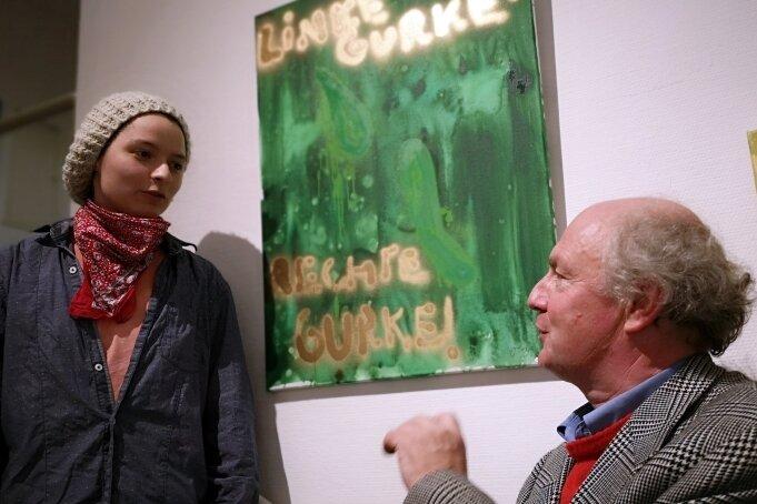 """Schräge Lieder unter der """"Luther-Palme"""": Jens Ausderwäsche und Osmar Osten (rechts), dahinter das Bild """"Linke Gurken - rechte Gurken""""."""