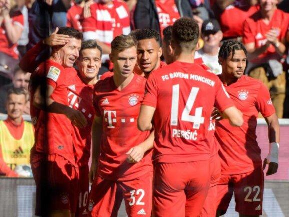 Die Spieler von Bayern München jubeln mit Torschütze Robert Lewandowski (l) über die 1:0-Führung gegen Union Berlin.