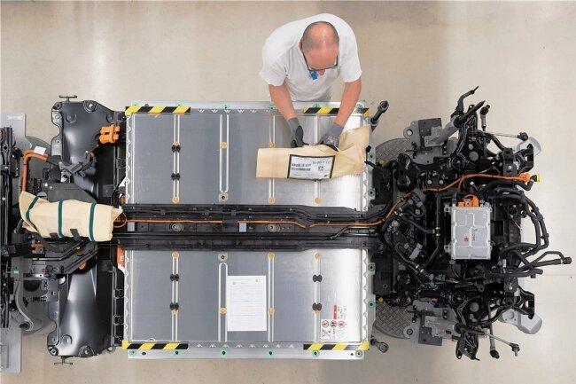 Ein VW-Mitarbeiter verkabelt in der Gläsernen Manufaktur in Dresden den Akku an einer Linie für den VW ID.3.
