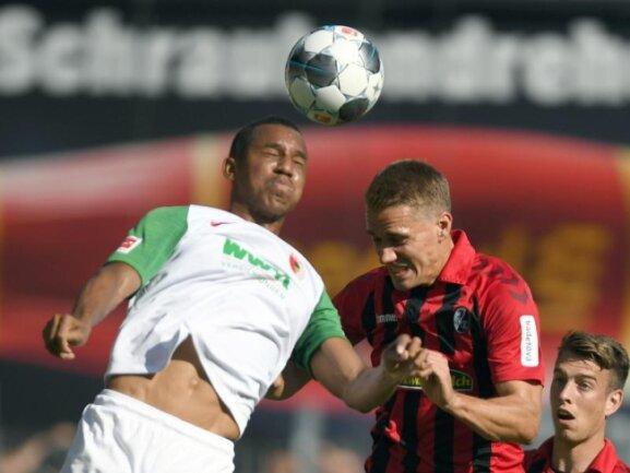 Der Augsburger Ohis Felix Uduokhai (l) und Nils Petersen vom SC Freiburg gegen zum Ball.