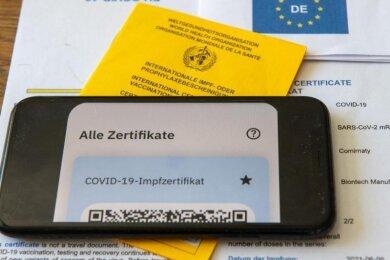 Ein Impfpass und ein Smartphone, auf dem die App CovPass läuft.