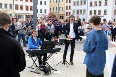 Domkantor Albrecht Koch (M.) dirigiert die Jugendkantorei des Freiberger Domes auf dem Obermarkt.