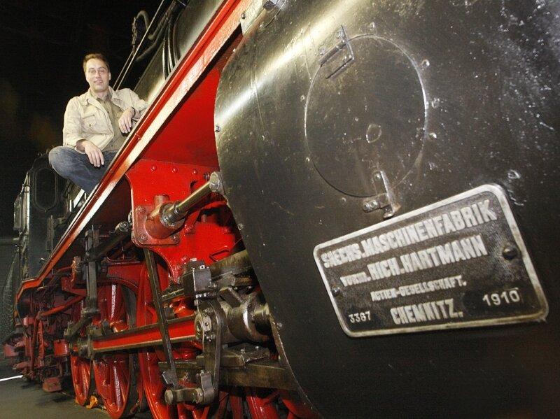 """Sven Liebold vom Vorstand des Vereins Sächsisches Eisenbahnmuseum liebt Eisenbahnen. Hier sitzt er auf einer Hartmann-Lokomotive der Baureihe 38 aus dem Jahr 1910. Die """"Hegel""""-Lok ist nicht ganz so groß, dafür älter. Seit 1886 fuhr sie im Dienst der Sächsischen Staatseisenbahn."""