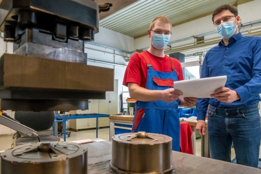 Geschäftsführer Martin Dietze schaut sich mit Werkzeugmechaniker Maik Haase (v.r.) Einsätze für Spritzgußwerkzeuge an.