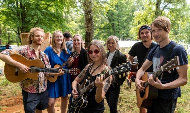 Während die Holzbildhauer ihre Kunstwerke aus Baumstämmen herausarbeiten, erschaffen die Teilnehmer des Singer-Songwriter-Sommercamps um Leiterin Anika Jankowski (3. v. l.) neue Songs.