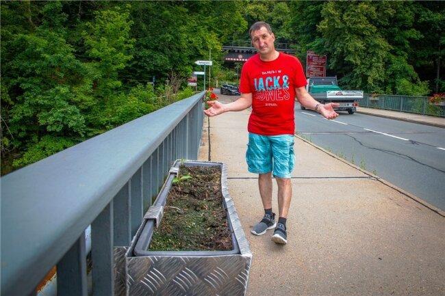 Jens Preusche kümmert sich um die Blumenkästen auf der Brücke. Die verschwundenen Pflanzen machen ihn ratlos.