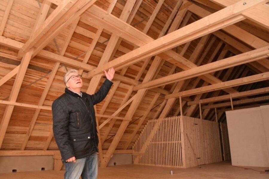 Oewog-Geschäftsführer Uwe Hirsch zeigt das neue Dach des Gebäudes. Es war beim Großfeuer vollständig zerstört worden.