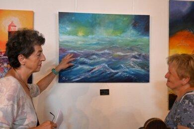 Elke Müller (links) und Brigitte Malzdorf beim Betrachten von Bildern mit Seelandschaften in der Elterleiner Kirche.
