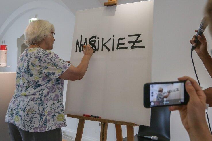 """Aus """"Nazikiez"""" wird """"Naschkiez"""": Aktivistin Irmela Mensah-Schramm (Jahrgang 1945) demonstrierte am Samstag in den Kunstsammlungen, wie sie Nazi-Parolen durch Übermalen ihrer Aussage beraubt. Rechts: Künstler Bernd Langer mit seinem Original-Entwurf des Antifa-Symbols. Die Arbeit wurde bei einer Auktion für mehr als 3600 Euro ersteigert."""