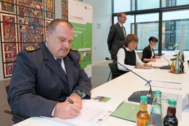 Polizeipräsident René Demmler, OB Pia Findeiß, Innenminister Roland Wöller (stehend) und Anja Herold-Beckmann vom Landespräventionsrat Sachsen (von links) bei der Vertragsunterschrift.