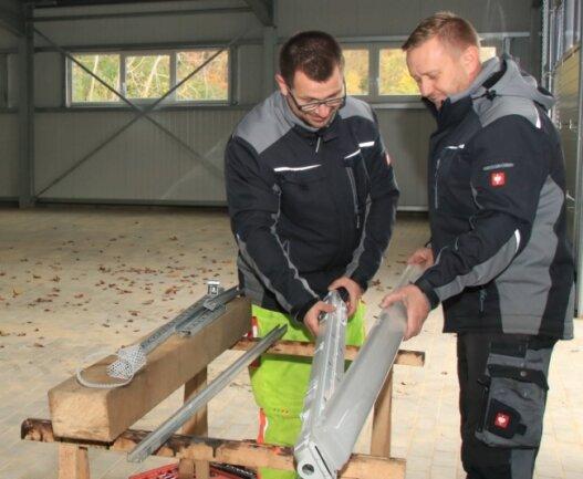 Steffen Möckel (links) und Rico Lechleiter vom Limbacher Bauhof erledigen in der neuen Halle in Eigenleistung der Gemeinde einige Vorbereitungsarbeiten für die Elektroinstallation.