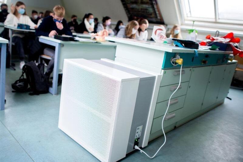 Ein Luftfiltergerät steht in einem Klassenraum.