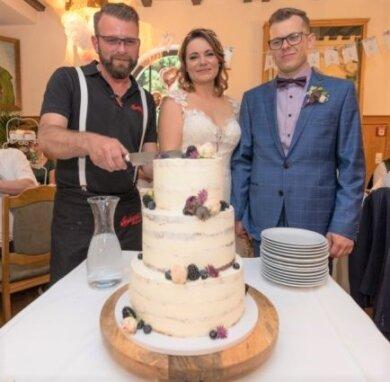 Sie haben ihren Eintrag in den Analen des neuen Berghotels auf dem Bärenstein sicher: Doreen und Danny Hunger (r.) waren das erste Hochzeitspaar, das bei Dennis Feist (l.) gefeiert hat.