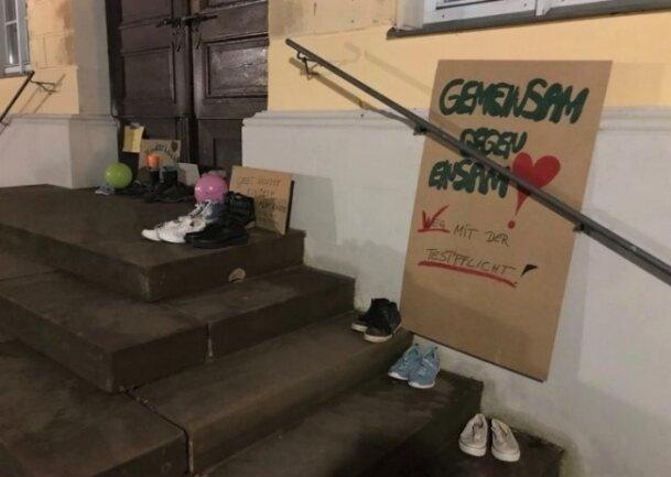 Auf der Rathaustreppe in Hainichen waren am Montagabend Kinderschuhe und Plakate abgestellt worden.