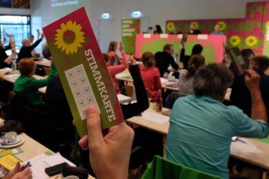 Delegierte der Landesversammlung der sächsischen Grünen halten am Samstag Stimmkarten in die Höhe.