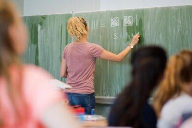 Eine junge Lehrerin schreibt im Unterricht an eine Schultafel.