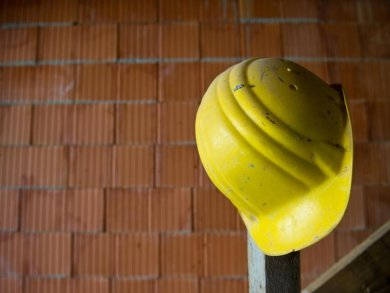 Ein Bauhelm hängt auf einer Baustelle.
