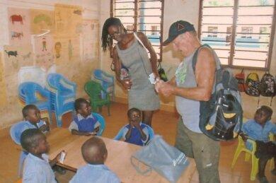 Werner Pforte bei einer Kindergruppe. Als Dolmetscherin hilft Faith, die vor Ort auch finanzielle Aufträge erledigt.