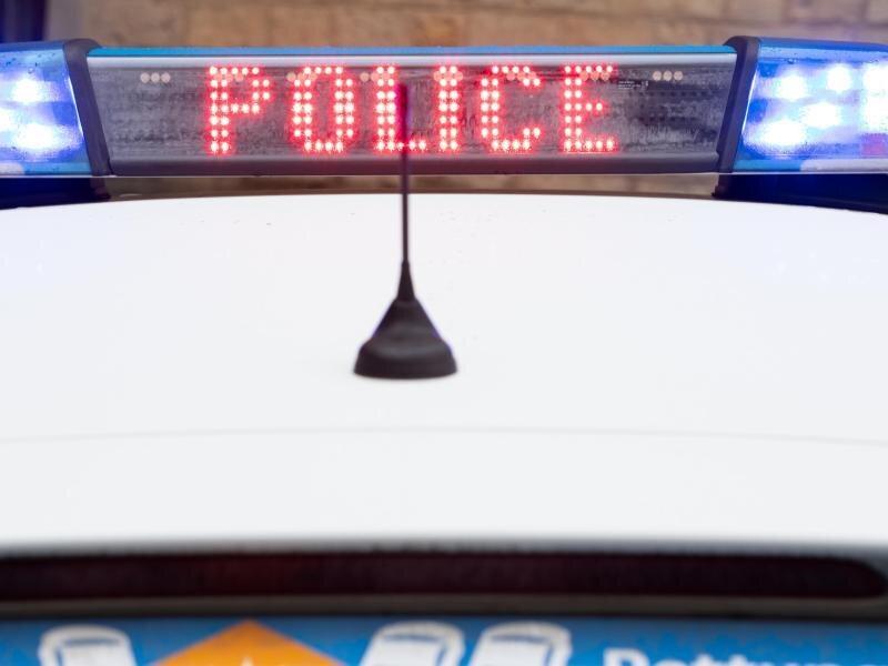 """""""Police"""" steht auf dem Display eines Polizeiwagens mit angeschaltetem Blaulicht."""
