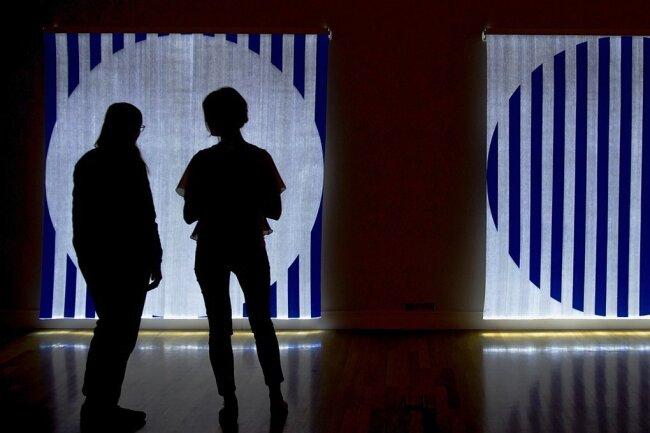 """Der Franzose, der dem Chemnitzer Schornstein Farbstreifen gab, ist in der Jubiläumsausstellung auch vertreten: Von Daniel Buren, dessen Markenzeichen Streifen sind, wird dieses Werk namens """"Quand le Textile s'éclaire. Fibres optiques tissées - EE1 et FF1 bleu foncé, Diptychon"""" gezeigt."""
