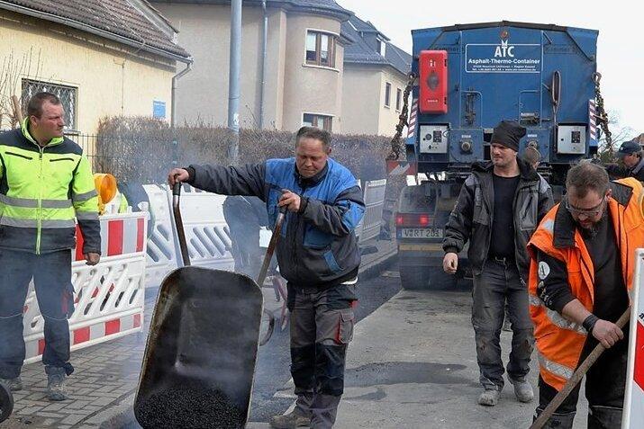 Bauarbeiter schließen eine Baugrube für den Breitbandausbau in Meerane.